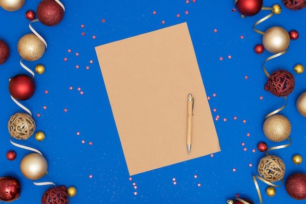 Kerstversiering en blanco ambachtelijke vel papier en pen op blauw papier achtergrond.