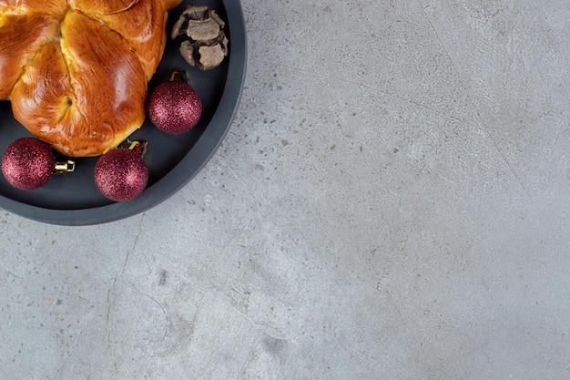 Kerstversiering en een broodje op een schaal op marmer