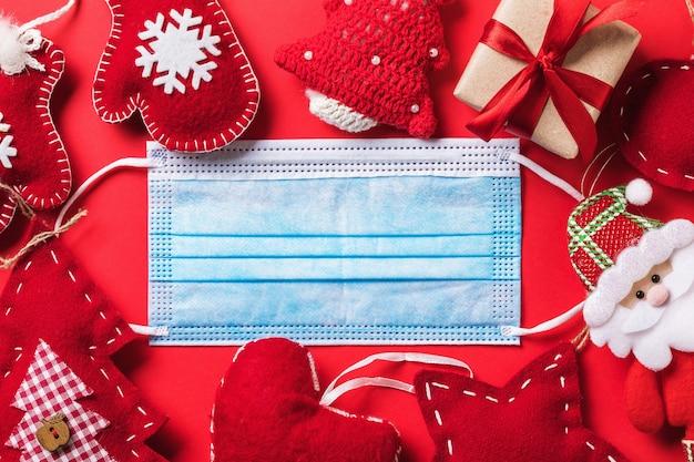 Kerstversiering en een wegwerp medisch masker op een rode achtergrond