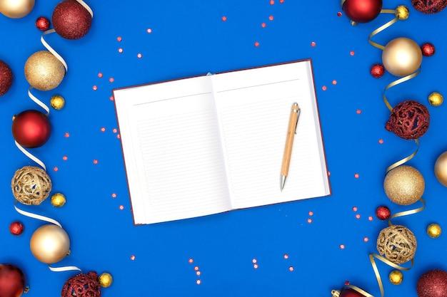 Kerstversiering en notebook en pen op blauw papier achtergrond.