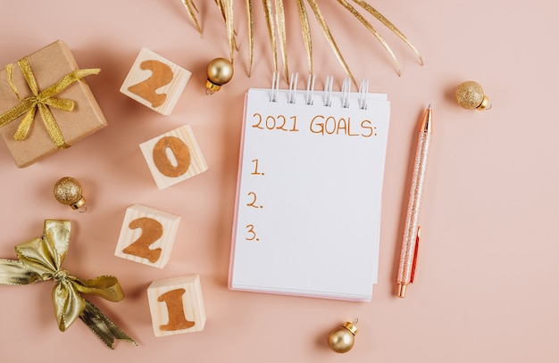 Kerstversiering en notebook met verlanglijstje op poederachtige achtergrond.