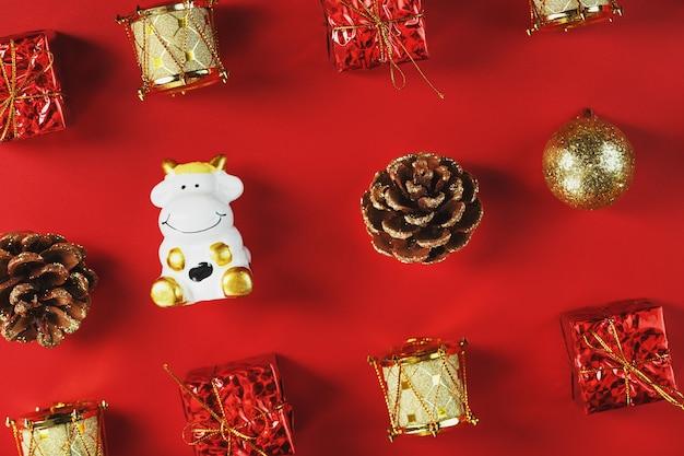 Kerstversiering en speelgoed met een koe op een rode muur. de stier is een symbool van het nieuwe jaar 2021.