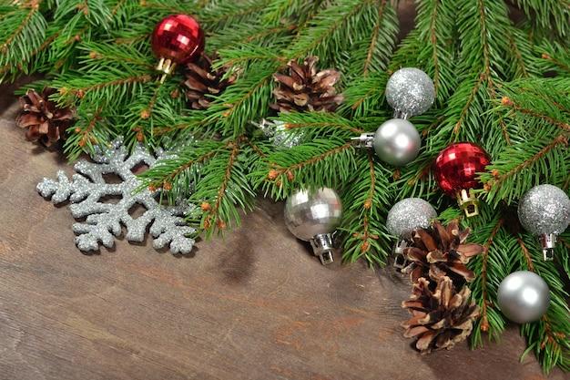 Kerstversiering en vuren tak en kegels op een houten achtergrond