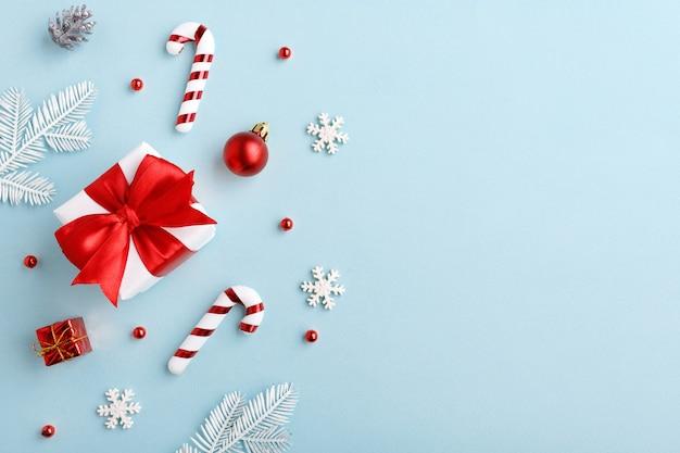 Kerstversiering geschenken, zuurstokken, ballen, sneeuwvlokken op pastelblauw papier