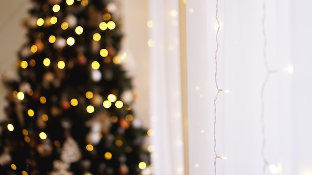 Kerstversiering, kerstboom, geschenken, nieuwjaar in gouden kleur - onscherpe achtergrond