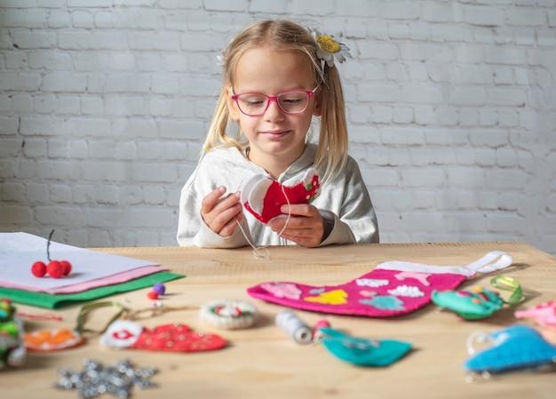 Kerstversiering, klein meisje dat kerstviltdecoratie maakt