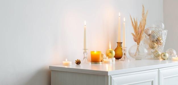 Kerstversiering met brandende kaarsen in witte kamer