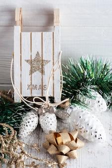 Kerstversiering met houten slee en gouden strik