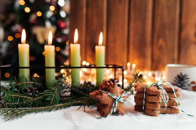 Kerstversiering met kaarsen, dennentakken en peperkoek