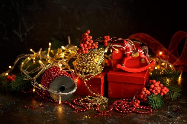 Kerstversiering met lichten, speelgoed en rode geschenkdozen op donker