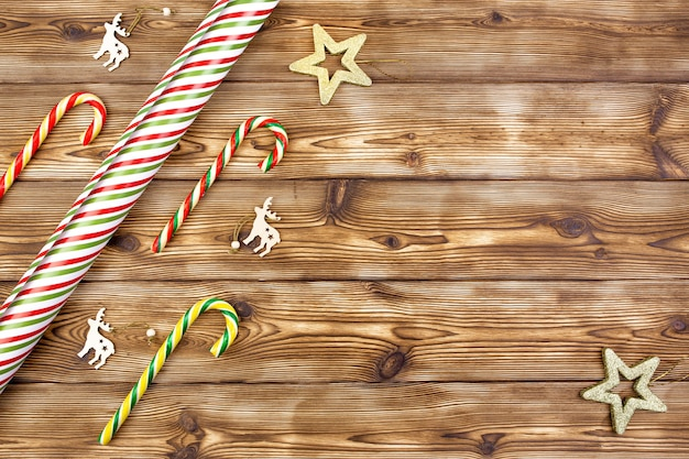 Kerstversiering met strepen inpakpapier lollies op houten achtergrond