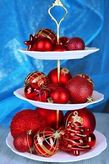 Kerstversiering op dessertstandaard, op gekleurde achtergrond