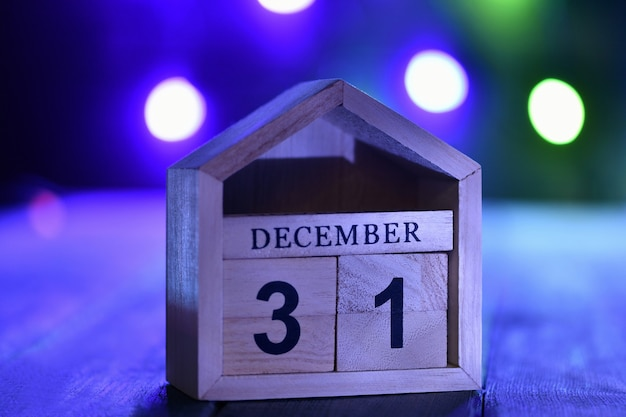 Kerstversiering op een houten muur: houten blokjes met de cijfers 31 december in het donker, en wazige slinger. selectieve aandacht