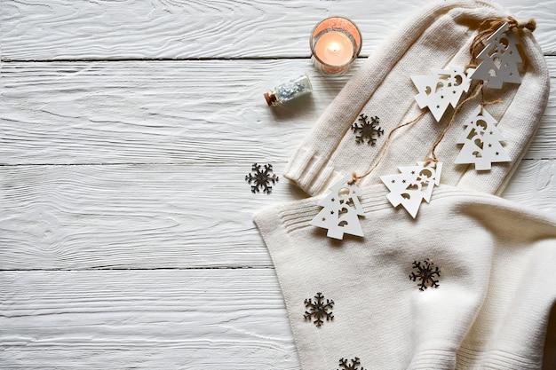 Kerstversiering op een witte houten achtergrond. witte wollen muts en sjaal, witte houten dennen aan een veter, zilveren sneeuwvlokken, kaars en decoratieve fles met glitters. winter achtergrond.