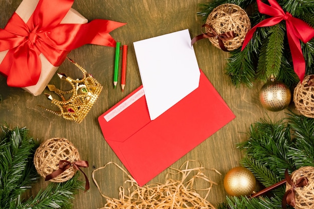 Kerstversiering op groene houten gestructureerde achtergrond, bovenaanzicht, vrije ruimte voor ontwerp, brief op rode loper en kleine kronen voor meisjes