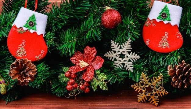 Kerstversiering op houten ondergrond, nep dennentakken, kerstsokken en verschillende soorten ornamenten rekwisieten genomen van hoog boven de kijkhoek.