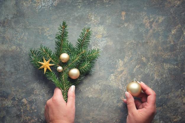 Kerstversiering, plat leggen met handen met fir twijgen versierd met gouden snuisterijen, kerstballen en sterren. plat lag op donkere gestructureerde tafel.