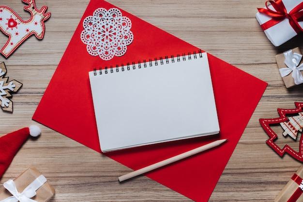 Kerstversiering, speelgoed en geschenkdozen op houten tafel. leeg schetsboek met een potlood om de beste wensen te schrijven.
