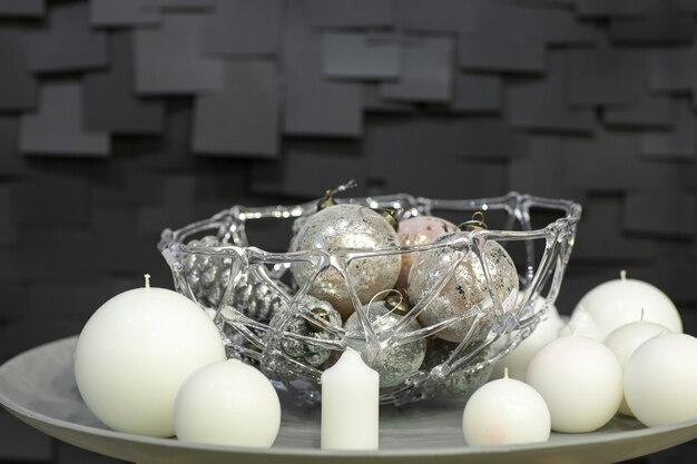 Kerstversiering van bolvormige kaarsen en vazen met kerstspeelgoed op een witte plaat