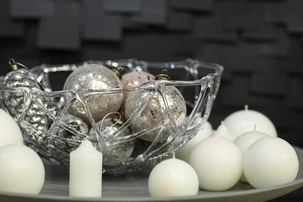 Kerstversiering van bolvormige kaarsen en vazen met kerstspeelgoed