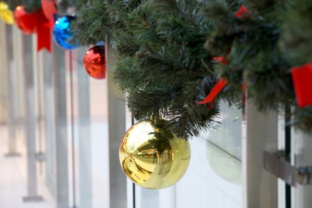 Kerstversiering van winkelcentrum bollen, bogen en takken van een dennenboom