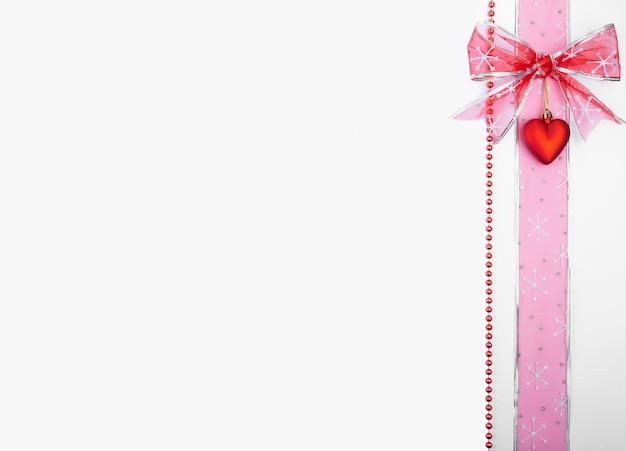 Kerstversiering verticaal geplaatst aan de zijkant van de afbeelding met copyspace op witte achtergrond, boog, hart, lint,