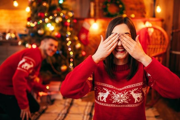 Kerstviering, echtgenoot maakt verrassing voor zijn vrouw, dennenboom met versiering. gelukkig liefdepaar viert kerstvakantie
