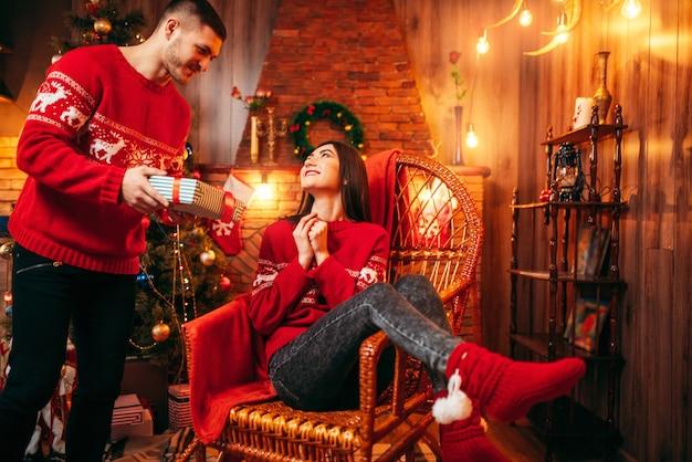 Kerstviering, man maakt geschenken aan zijn vrouw, dennenboom met decoratie. gelukkig liefdepaar viert kerstvakantie