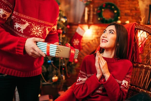 Kerstviering, mannelijke persoon maakt geschenk aan mooie jonge vrouw, dennenboom met decoratie. gelukkig liefdepaar viert kerstvakantie