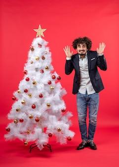 Kerstviering met bebaarde jongeman die vreselijk bang voor iets is en in de buurt van de kerstboom staat