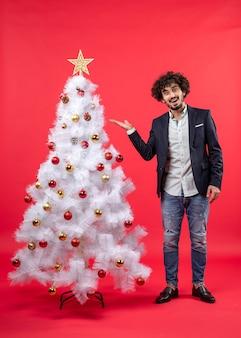 Kerstviering met bebaarde jongeman wijzende kerstboom