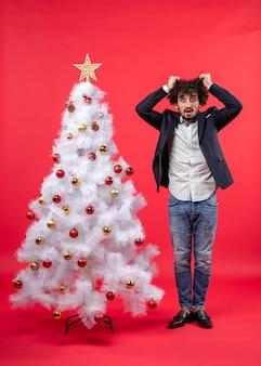 Kerstviering met een bebaarde jongeman die uitgeput is van alles en zich extreem nerveus voelt in de buurt van de kerstboom