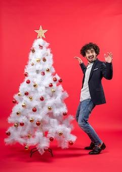 Kerstviering met gelukkig grappig opgewonden jongeman dansen in de buurt van de kerstboom