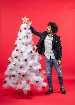 Kerstviering met gelukkige grappige jongeman tounching ster