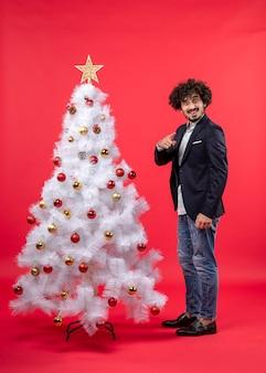 Kerstviering met jonge gelukkig opgewonden grappige man wijst iets staande in de buurt van de kerstboom