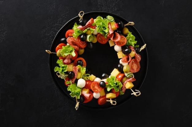 Kerstvoedsel krans van vakantie snacks canapeetjes groenten mozzarella kaas voor feestelijke kerstfeest