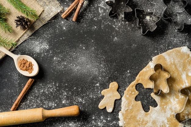 Kerstvoedselkader met peperkoekkoekjes, bakvormen op zwarte achtergrond met exemplaarruimte.