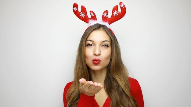 Kerstvrouw met rode lippen blaast luchtkus met rendierhoorns op haar hoofd