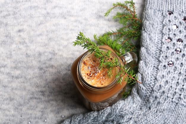 Kerstwinterkoffie met een sparrentak op een gebreide grijze achtergrond