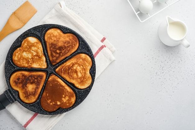 Kes in vorm van ontbijtharten in de pan met ingrediënten om te koken. gezond ontbijt of tussendoortje. ontbijt voor valentijnsdag. bovenaanzicht kopie ruimte.