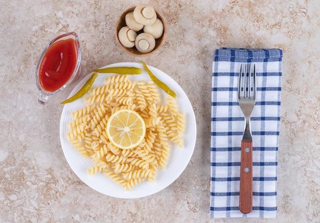 Ketchup, dressing voor dineropstelling met macaroni en vork op een handdoek op marmeren oppervlak.