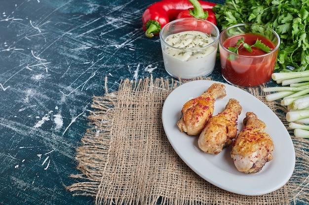 Ketchup en mayonaise sauzen met kruiden en rauwe kippenpoten.
