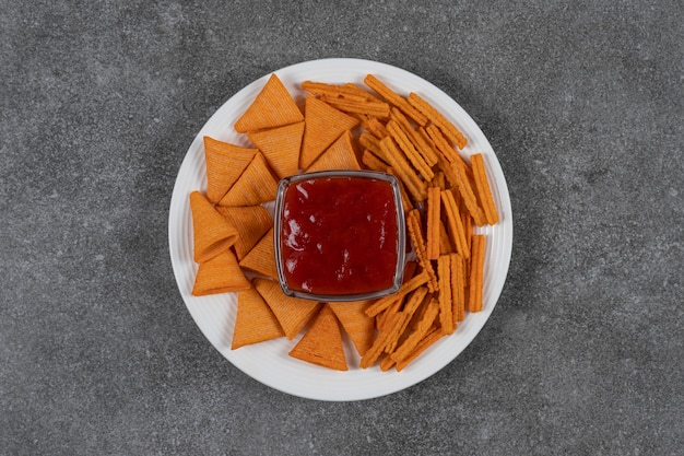 Ketchup, maïsspaanders en gedroogd brood op plaat op het marmeren oppervlak