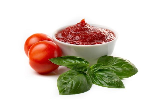 Ketchup (tomatenpuree) in een pan met basilicumbladeren en hele tomaten op een witte achtergrond.