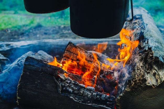 Ketel en waterkoker boven vreugdevuur. koken van voedsel op de natuur. diner buitenshuis. brandhout en takken in brand. actieve rust. kamperen in het bos.