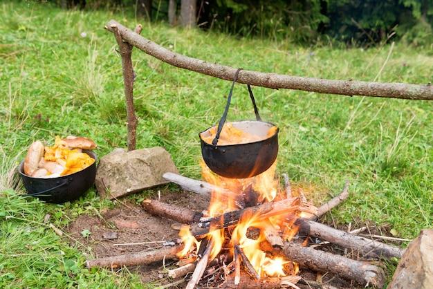 Ketel met kokend kokende eetbare paddestoelen op het vuur. buitenhaard in een kamp