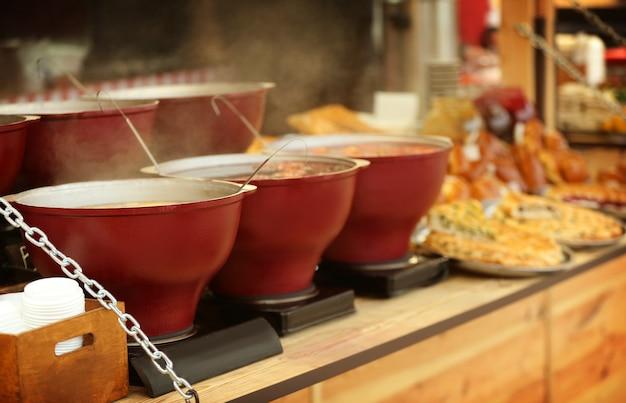 Ketels met glühwein op toonbank bij kerstmarktkiosk fair