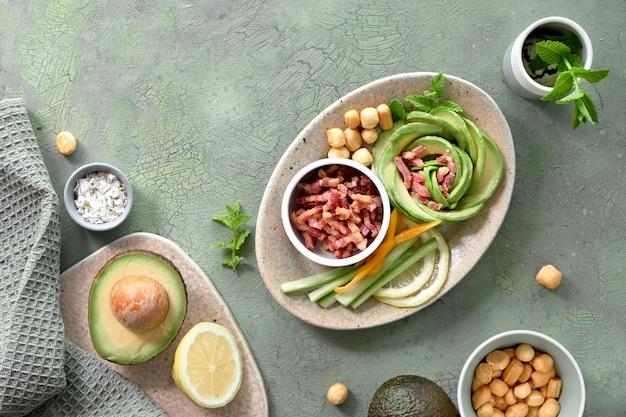 Keto dieet, bovenaanzicht van avocado rose salade met spekblokjes en gerookte kaas op groene tafel