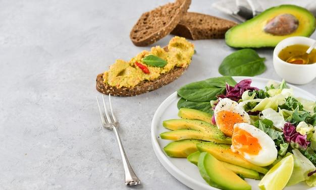 Keto dieet salade van avocado, boerenkool, eieren en spinazie.
