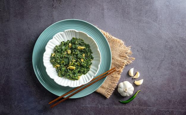 Keto dieet voedsel spinazie curry in witte kom en blauwe plaat met chopstick knoflook pepers op blauwe houten tafelblad weergave
